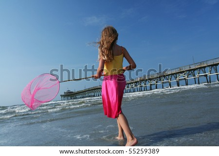 Beautiful young girl playing on the beach near the ocean. Fishing and looking for sea life using a cute pink net to match her dress. Rustic fishing pier in the background.