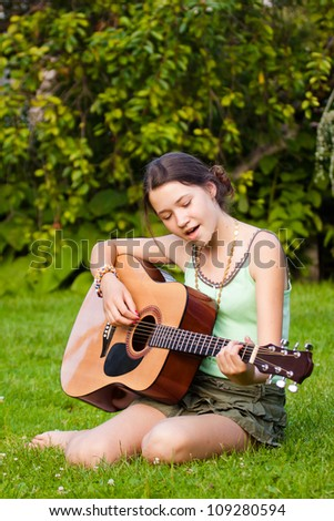 Beautiful young girl playing the guitar in nature - stock photo