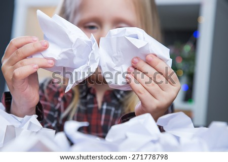 Beautiful young girl playing with crumpled paper balls - stock photo