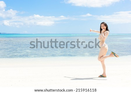 beautiful young girl pointing to the sea on tropical island beach