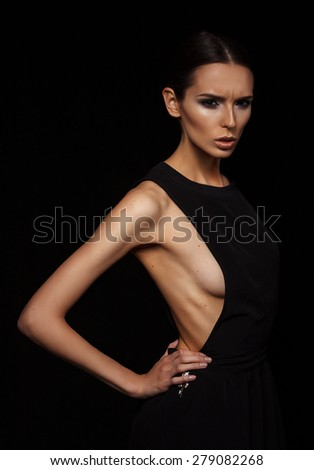 Beautiful young girl portrait in black dress posing on black background - stock photo