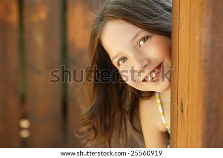 beautiful young girl portrait playing hidden behind the wooden door - stock photo