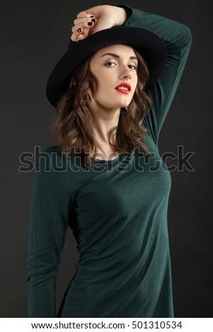 Beautiful young girl posing in a dress and hat.