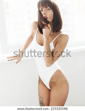 Beautiful young girl posing in white swimsuit - stock photo