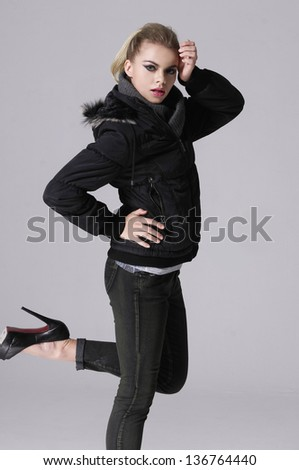beautiful young girl posing over gray, model in a black jacket - stock photo