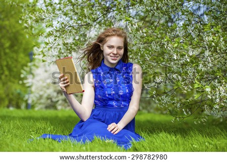 Beautiful young girl reading notebook under the flowering white apple tree