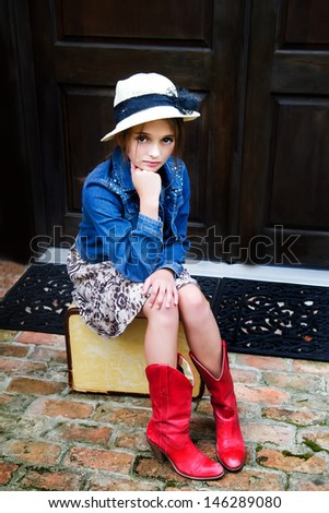 Beautiful young girl ready to travel with red boots, a hat and a suitcase - stock photo