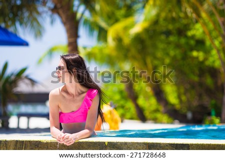 Beautiful young girl relaxing in the swimming pool - stock photo