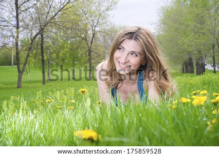 Beautiful young girl resting in meadow - stock photo
