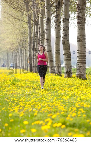 Beautiful young girl running in a field of dandelions - stock photo