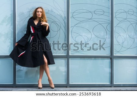 Beautiful young girl showing fashionable black coat on gray wall background - stock photo
