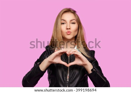 Beautiful young girl shows emotion on a purple background. Girl shows heart. Girl surprised what they see on the palm - stock photo
