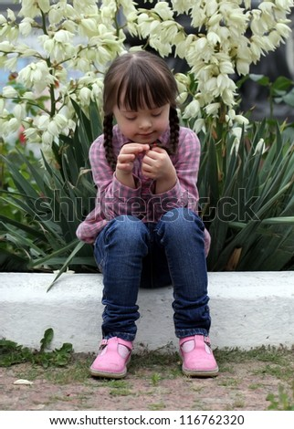 Beautiful young girl siting on flowers background. - stock photo