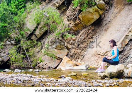 beautiful young girl sits on a rock in the river and draws from life
