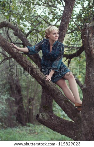 beautiful  young girl sitting on a tree branch