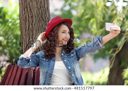 Beautiful young girl sitting on bench in park and taking selfie
