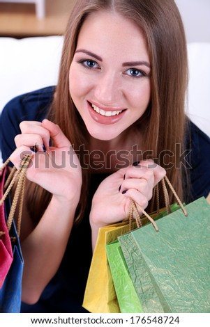 Beautiful young girl  sitting on sofa with shopping bags, close-up