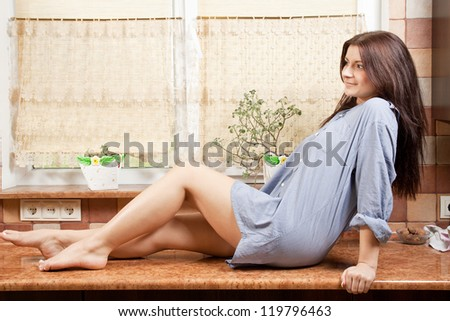 beautiful young girl sitting on table in the kitchen