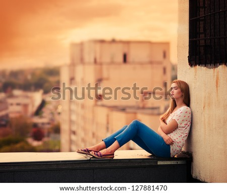 beautiful young girl sitting on the roof - stock photo