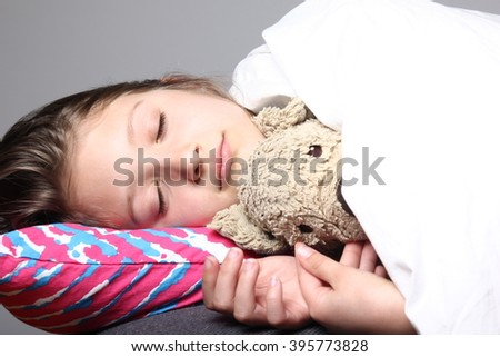 Beautiful young girl sleeping in bed - stock photo
