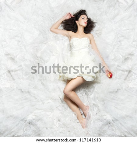 Beautiful young girl sleeping on white bed with with apple in her hand - stock photo