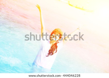 Beautiful young girl splashing the water in the sea with color filters