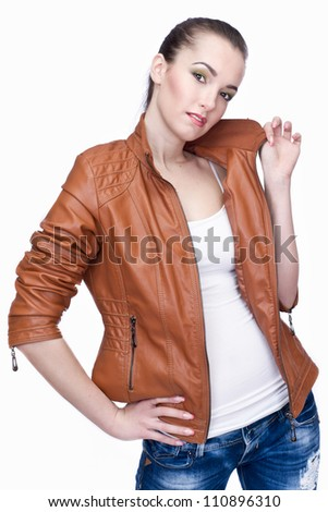 Beautiful young girl standing in the leather jacket - stock photo