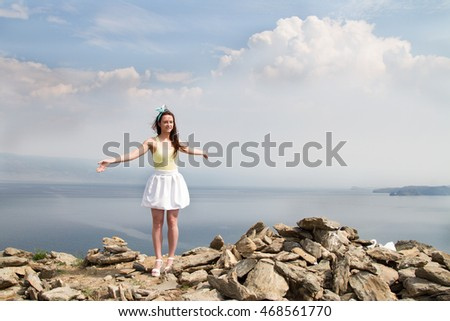 Beautiful young girl standing on a high mountain in the background of Lake Baikal