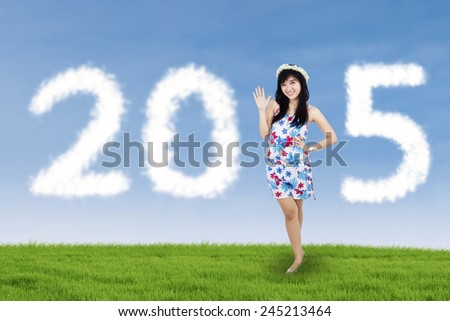 Beautiful young girl standing on the field and forming numbers 2015