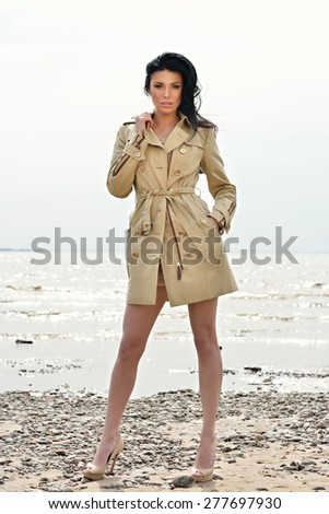 Beautiful young girl stands in a coat on the sand in windy weather