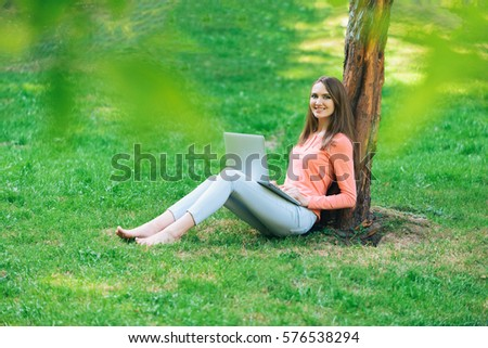 Beautiful young girl student using portable laptop computer while sitting in the park.