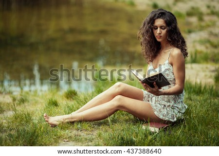 Beautiful young girl studying on green grass. Reading books