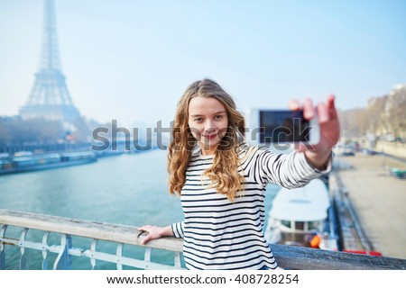 Beautiful young girl taking funny selfie with her mobile phone near the Eiffel tower - stock photo