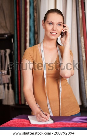 beautiful young girl talking on phone. waist up brunette standing in store and writing - stock photo