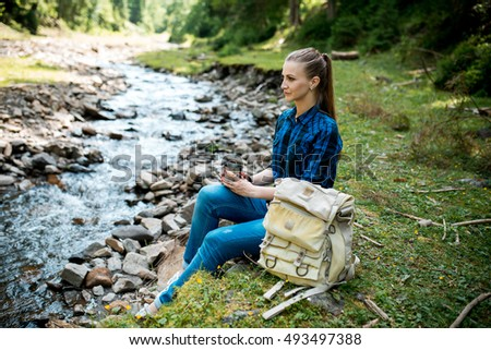 beautiful young girl tourist with backpack Hiking on the mountain river