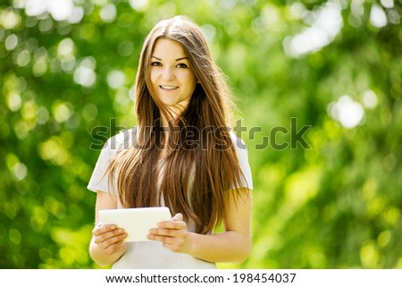 Beautiful young girl using a tablet computer in a leafy green park navigating the touchscreen with her finger , with copyspace