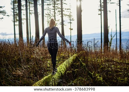 beautiful young girl walking in forest in running clothes standing on log - stock photo