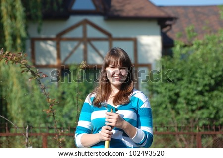 Beautiful young girl watering garden