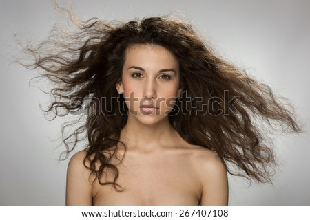 Beautiful young girl waving her hair on gray background