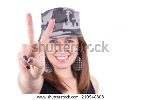 Beautiful young girl wearing a military cap gesturing peace sign isolated on white selective focus - stock photo