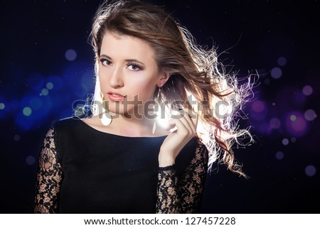 Beautiful young Girl wearing evening dress with Long Hair on Blinking Background. Bokeh