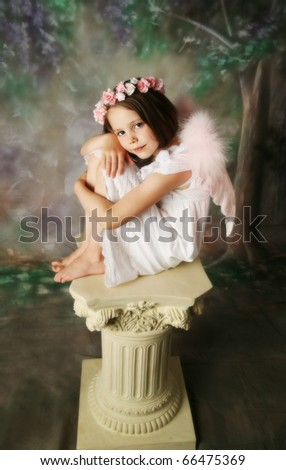 Beautiful young girl wearing pink angel wings and flower halo sitting on a pedestal - stock photo