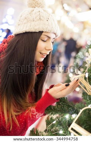 Beautiful young girl went shopping for Christmas presents in decorated mall with many bright lights,fur trees.Attractive young shopper girl go shopping at the mall,buy holidays presents for New Year