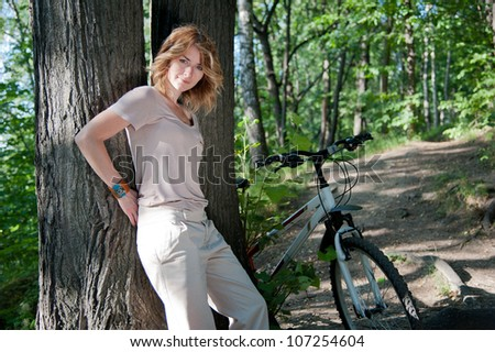 Beautiful young girl with a bicycle near the tree