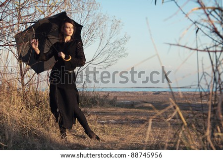 Beautiful young girl with a black umbrella stands against the background of autumn trees and the beach.