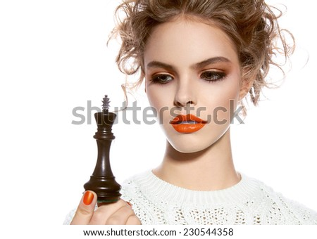 Beautiful young girl with a bright evening make-up, orange, scarlet lipstick, rosy cheeks, eye shadow, nail polish, blonde curly hair dressed in winter white knitted sweater holding a king chess piece - stock photo