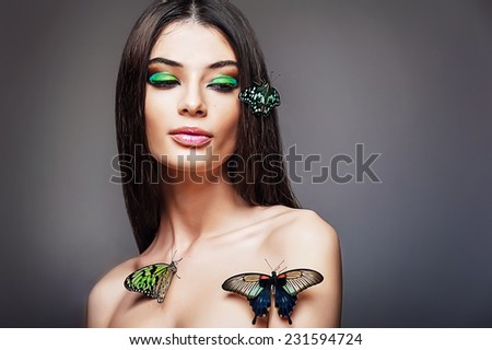 Beautiful young girl with a butterflies - stock photo