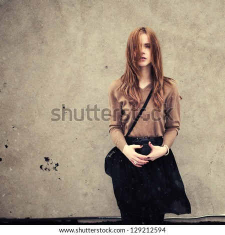 beautiful young girl with a camera on the background wall. girl is dressed in the style of hipster - stock photo