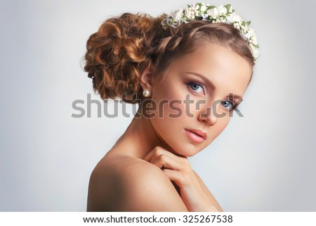 Beautiful young girl with a floral ornament in her hair.Beautiful Woman Touching her Face. Youth and Skin Care Concept on white background - stock photo