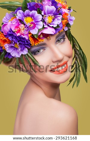 Beautiful young girl with a floral ornament in her hair, bouquet on head, looking at camera with blue eyes on yellow background. Developed from RAW, edited with special care and attention